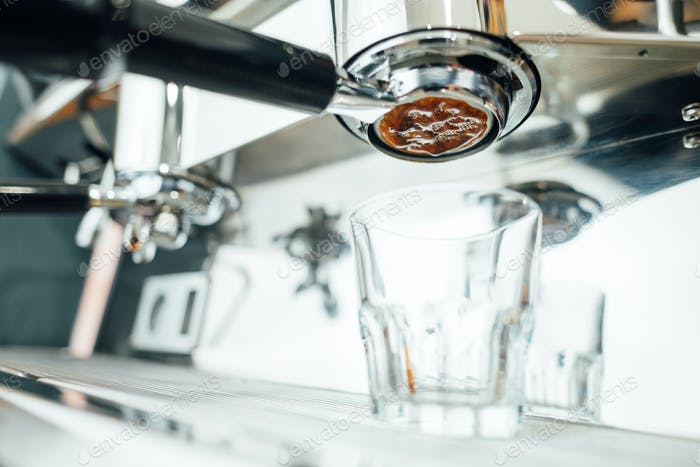 start of the espresso extraction process from bottomless portafilter in a glass cup