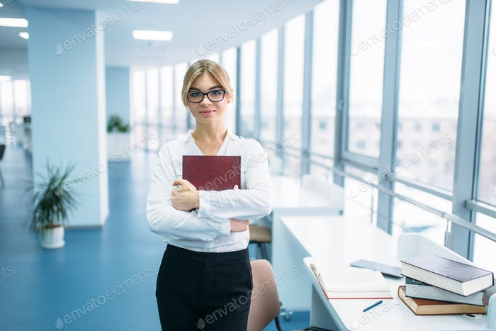 Cute young woman with book in library