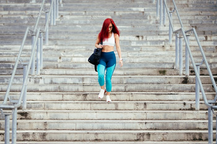 Woman preparing for training on stadium stairs. Portrait of professional athlete working out