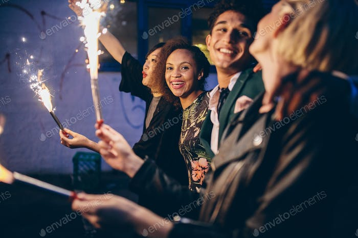 Group of friends partying and enjoying out with sparklers