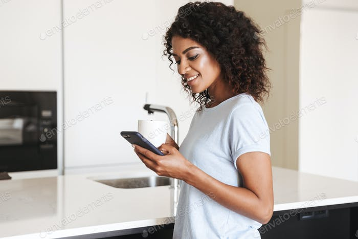 Happy african woman using mobile phone