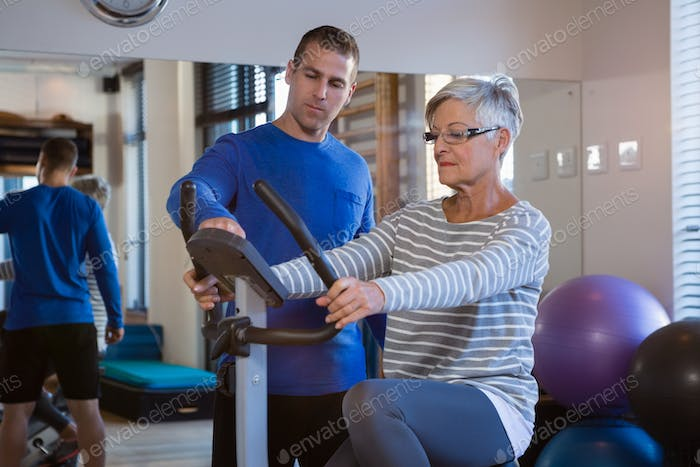Physiotherapist showing workout record on exercise bike