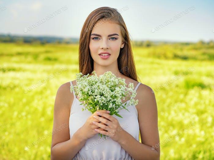 Glückliche und lächelnde schöne Frau im Freien mit Blumen in den Händen