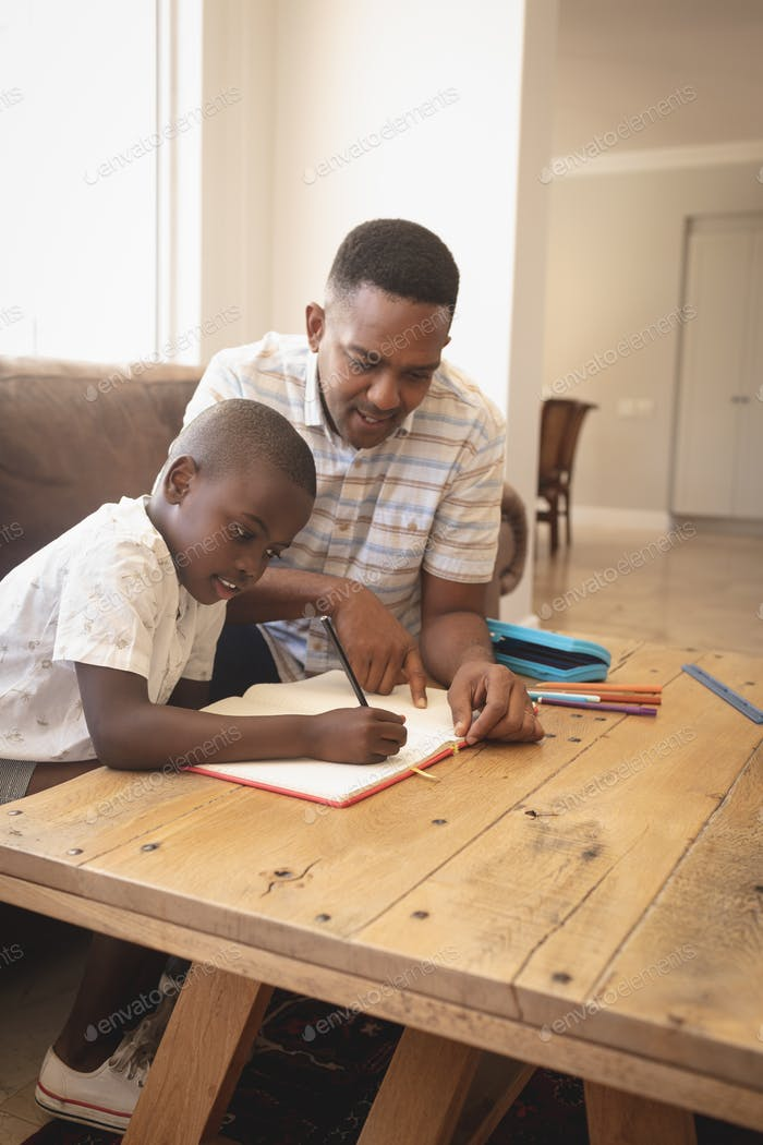 Front view of African American father helping his son with homework at table in a comfortable home