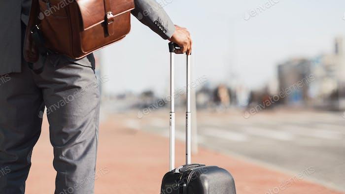 Неузнаваемый джентльмен в деловом путешествии стоит с чемоданом на открытом воздухе, Панорама