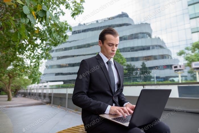 Young businessman sitting and using laptop computer in city