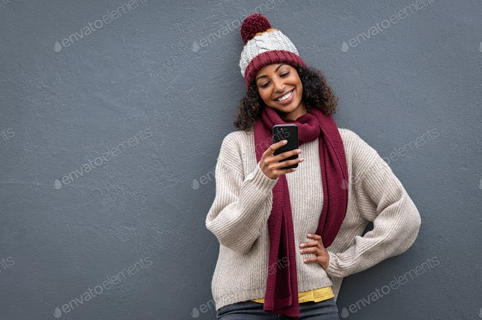 Young black woman in winter clothes using smartphone