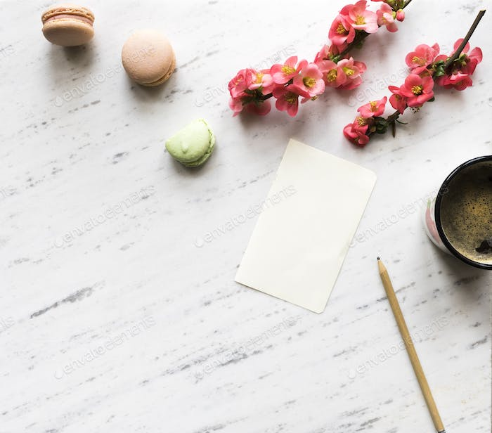 Top view of notebook, coffee, macarons and flowers on marble bac