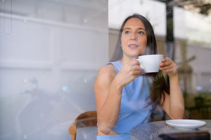 Young thoughtful businesswoman drinking coffee while looking through the window at the cafe