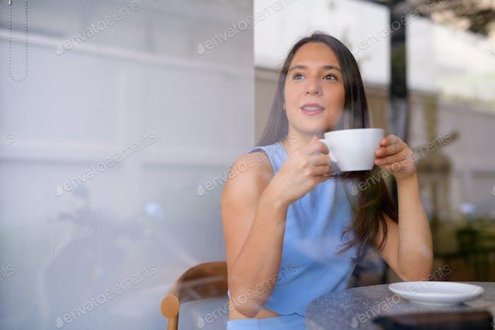 Junge nachdenkliche Geschäftsfrau trinken Kaffee beim Blick durch das Fenster im Café