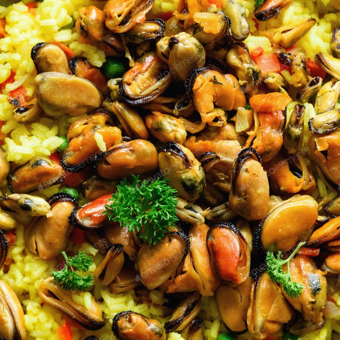 Traditional spanish seafood paella in pan rice, peas, shrimps, mussels, squid on light grey concrete