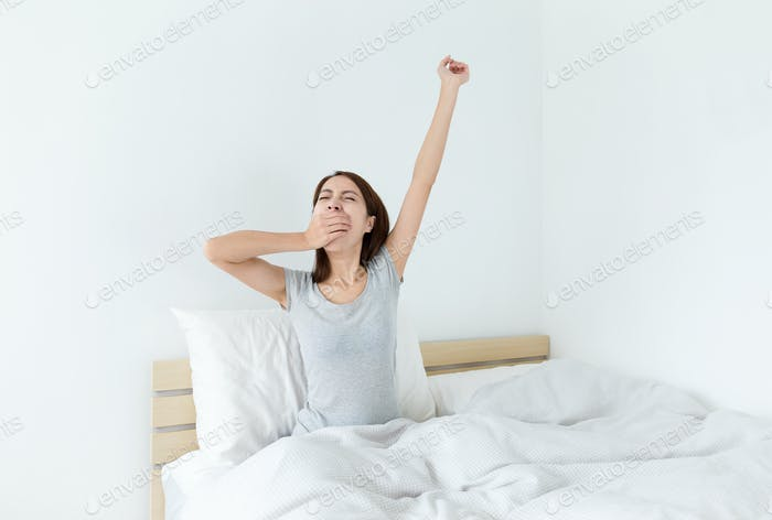 Woman waking up in her bedroom