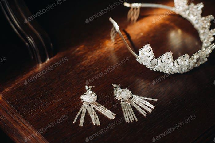 Hochzeitskrone für die Braut und Ohrringe liegen auf dem Rankgitter