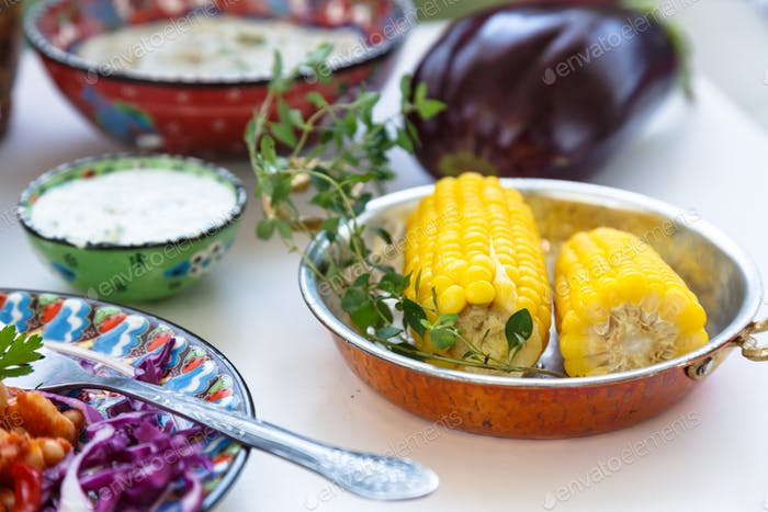 Corn elotes in copper pan. Mediterranian meze