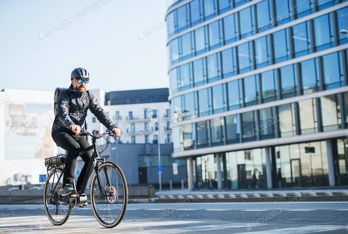 A male bicycle courier delivering packages in city. Copy space.
