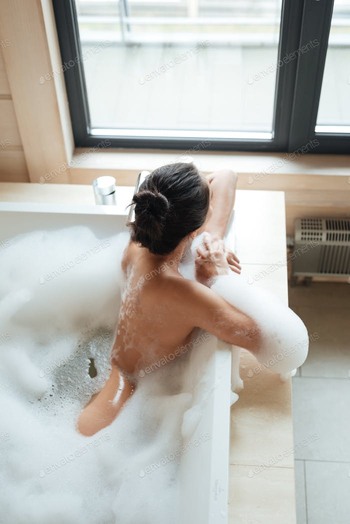 Attractive naked young woman sitting in bathtub with foam