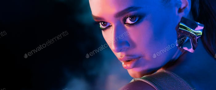 Fashion woman in neon light and smoke, panorama