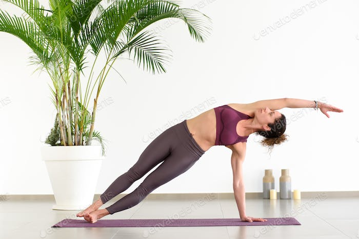 Woman doing side plank pose in yoga