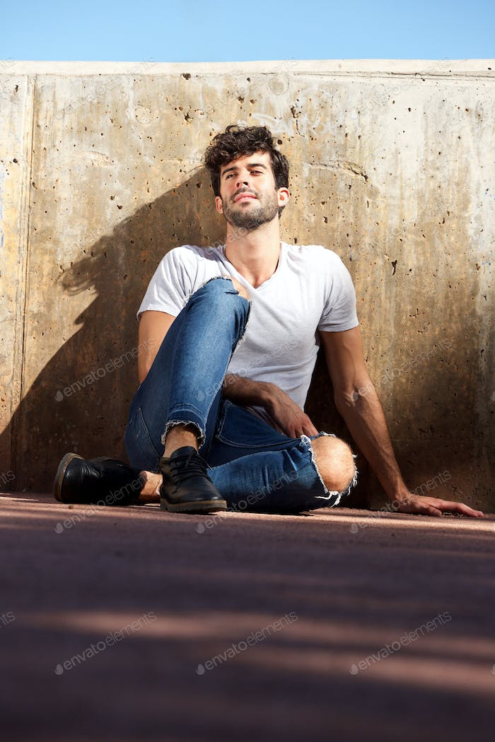 Young man sitting by concrete wall with eyes closed