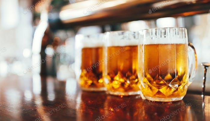 Glasses of light beer on a dark pub