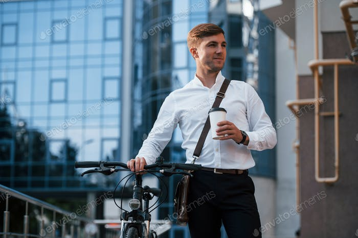 Conception of ecology. Businessman in formal clothes with black bicycle is in the city