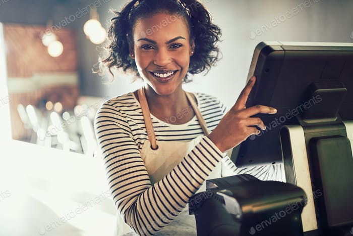 Smiling young African waitress working in a trendy restaurant