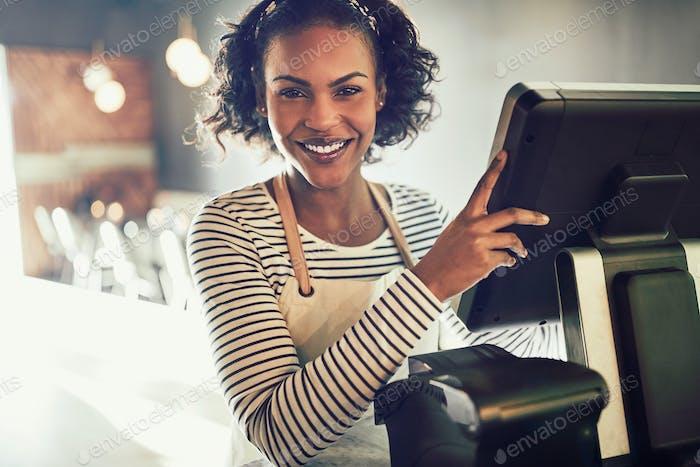 Lächelnde junge afrikanische Kellnerin arbeitet in einem trendigen Restaurant