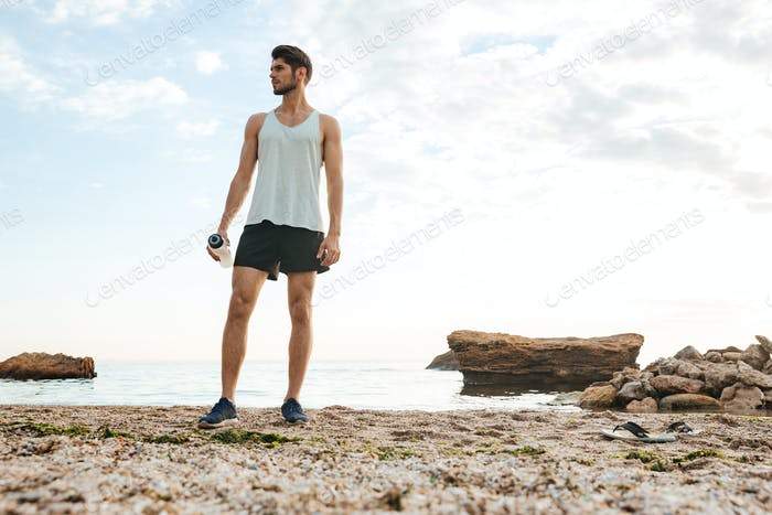 Man athlete resting after jogging at the beach