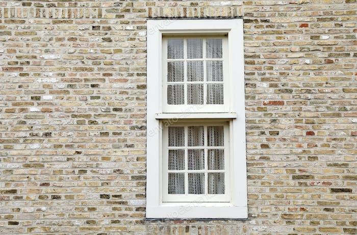 weißes Holzfenster auf Ziegelmauer