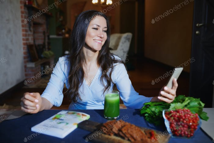 Woman at the table with healthy food making mobile photo selfie for her Internet blog