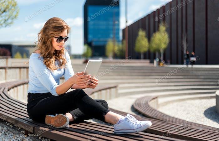 Junge Frau surfen im Internet mit Tablet im kostenlosen WLAN-Bereich im Stadtraum