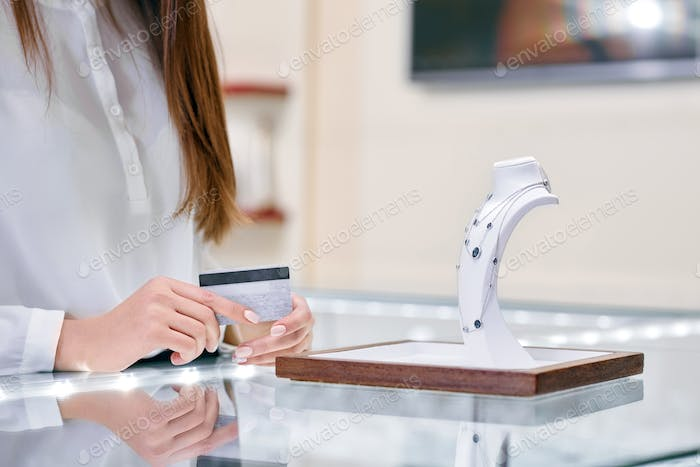 Woman is holding credit card in her hands and standing near the necklace in a jewelry shop