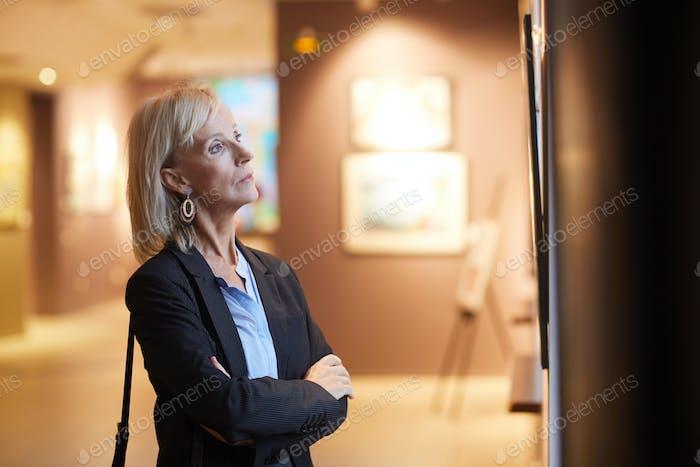 Reife Frau Blick auf Gemälde in Kunstgalerie