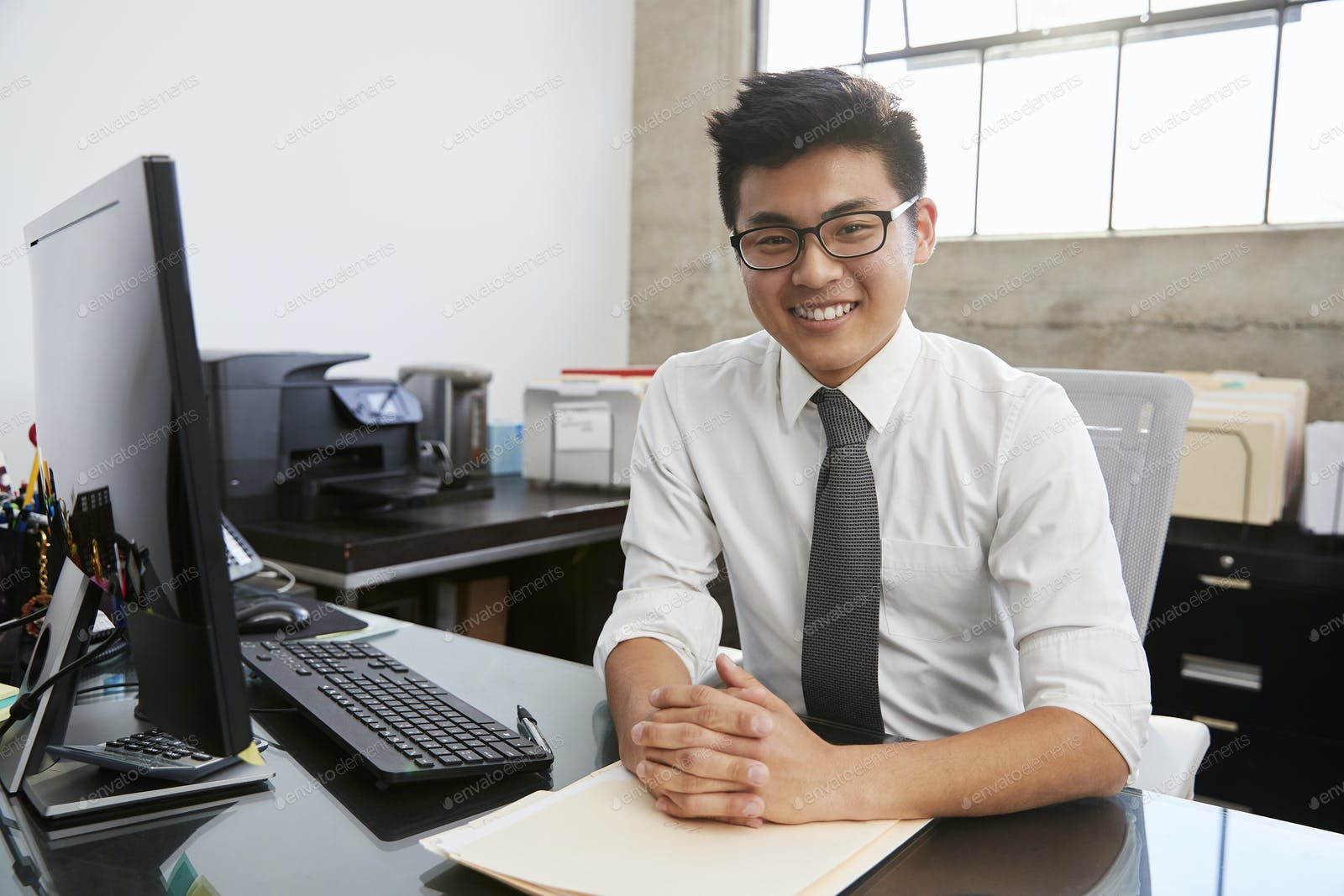 Young Asian male professional at desk smiling to camera photo by  monkeybusiness on Envato Elements