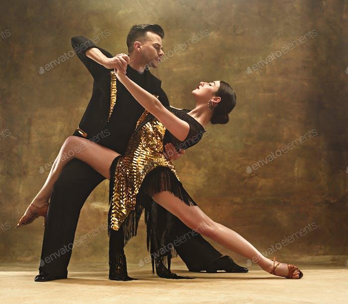 Tanz Ballsaal Paar in Gold Kleid Tanz auf Studio Hintergrund.