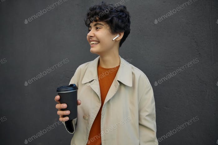 Positive young attractive brunette woman with short haircut keeping takeaway coffee