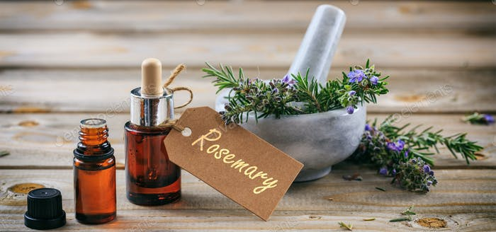 Rosemary essential oil and fresh blooming twig in a mortar, wooden table, tag with text rosemary