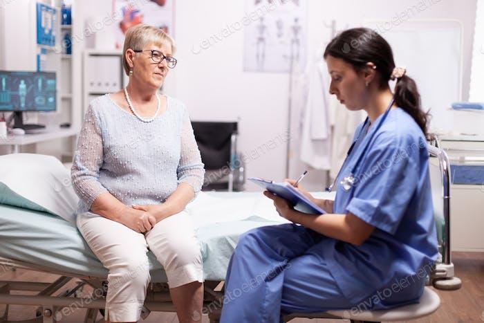 Nurse writing prescription on clipboard
