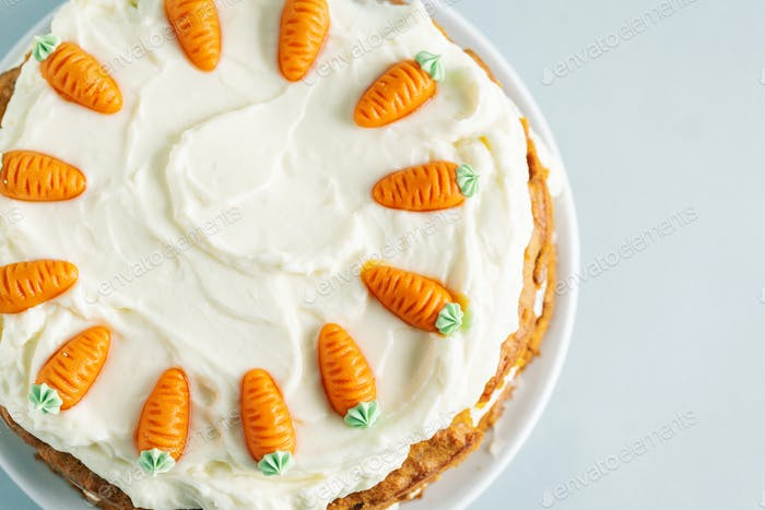 Easter carrot cake with frosting on blue background