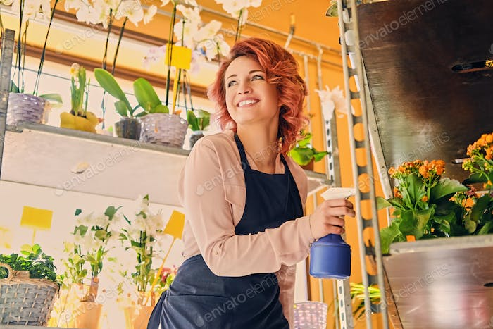 Female watering flowers in a market shop.