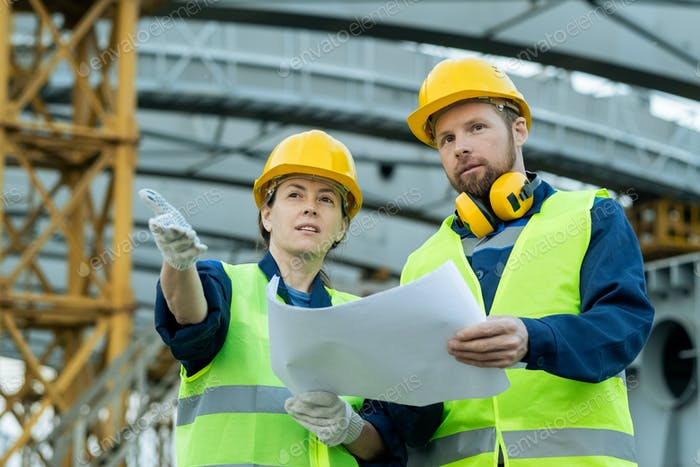 Two builders with blueprint discussing construction site