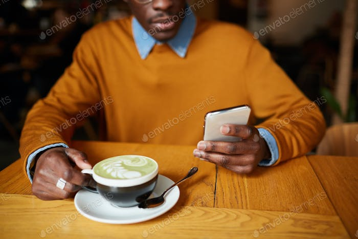 African Man Using Smartphone in Coffee Shop