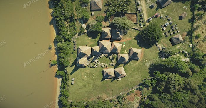 Aerial top down tropic countryside with ornately roofs cottages, houses of traditional village
