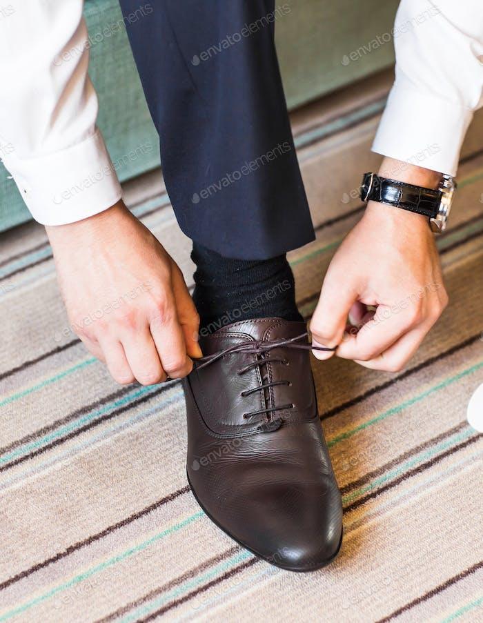 Nahaufnahme junger Mann binden elegante Schuhe drinnen