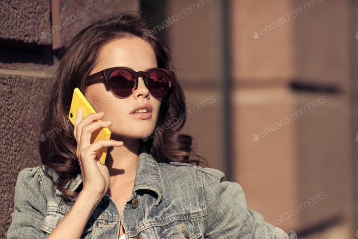 Young Woman Talking On Phone. City Street On Background.