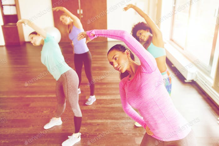 group of women exercising and stretching in gym