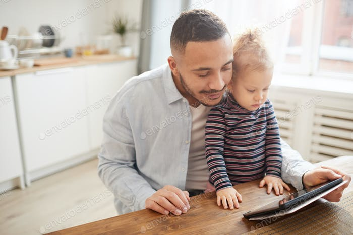 Caring Father Using Digital Tablet with Cute Little Girl