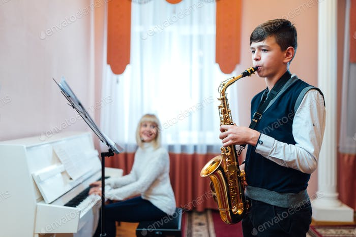 boy learns to play the saxophone in a music lesson