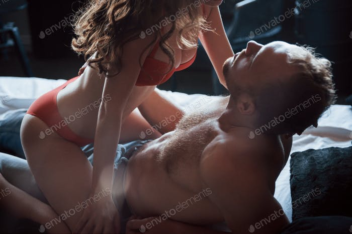 Attractive young lovers have couples playing together in bed, wearing sexy lingerie in a hotel room
