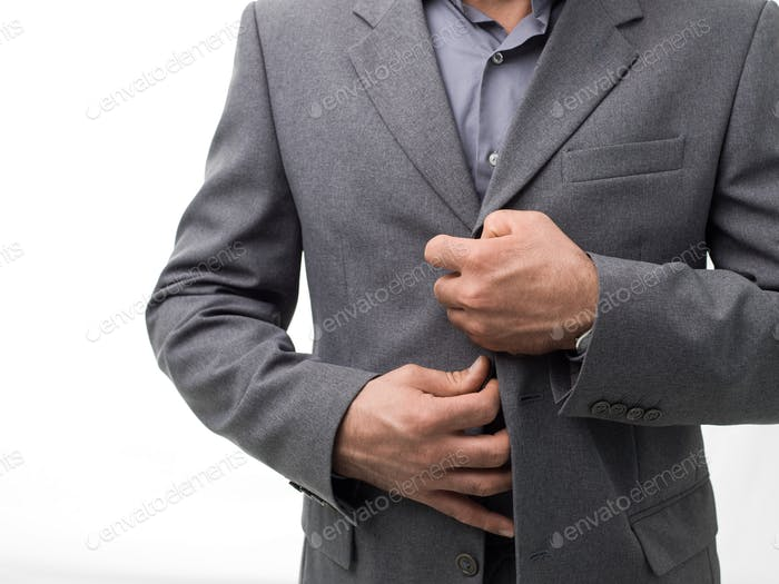Businessman unbuttoning his jacket